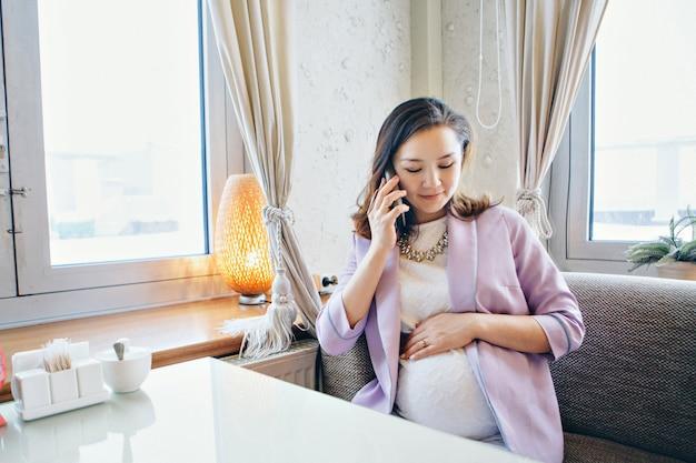 Eine schwangere frau streichelt ihren bauch.