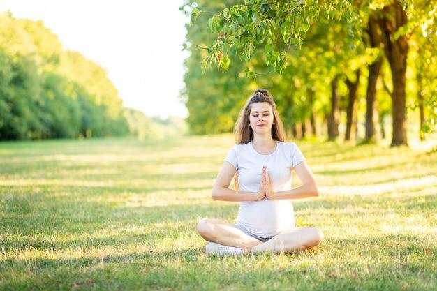 Eine schwangere frau treibt im sommer sport in der natur, yoga für schwangere frauen an der frischen luft
