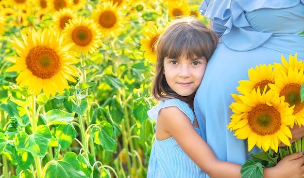 Eine schwangere frau und ihr kind in einem feld von sonnenblumen