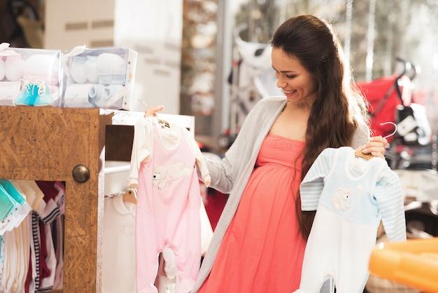 Eine schwangere frau wählt babywaren im speicher.