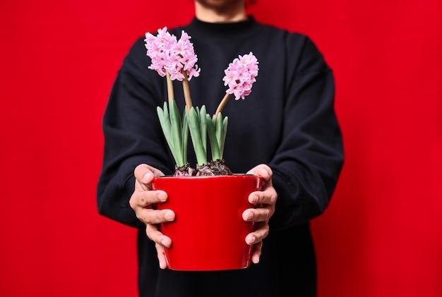 Eine schwarz gekleidete frau hält einen roten blumentopf mit rosa hyazinthen an einer roten wand