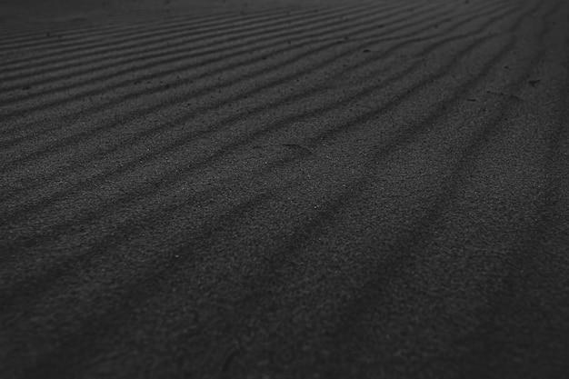 Eine schwarz-weiß-super-textur und ein sich wiederholender hintergrund des sandes des strandes mit einem großen muster