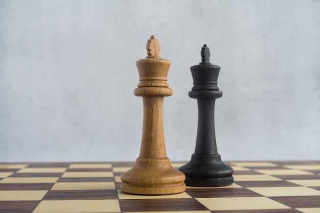 Eine schwarze dame nähert sich einem weißen könig auf dem schachbrett