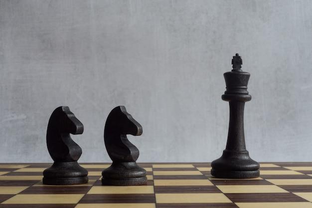 Eine schwarze königin und zwei schwarze pferde auf dem schachbrett