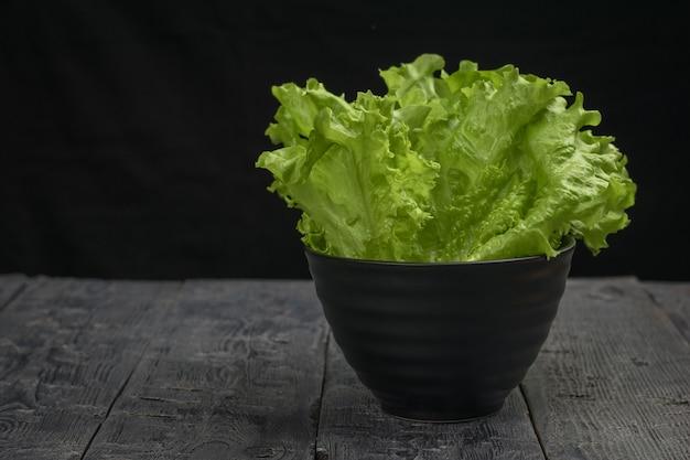 Eine schwarze schüssel mit salatblättern auf einem schwarzen holztisch