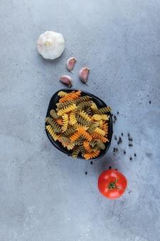 Eine schwarze schüssel voller bunter makkaroni mit frischen roten tomaten und knoblauch auf einer steinoberfläche.