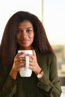 Eine schwarze studentin in einem büro hält
