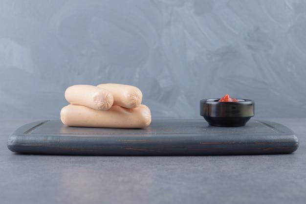 Eine schwarze tafel mit gekochten würstchen mit ketchup