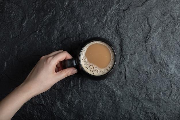 Eine schwarze tasse kaffee auf schwarz.