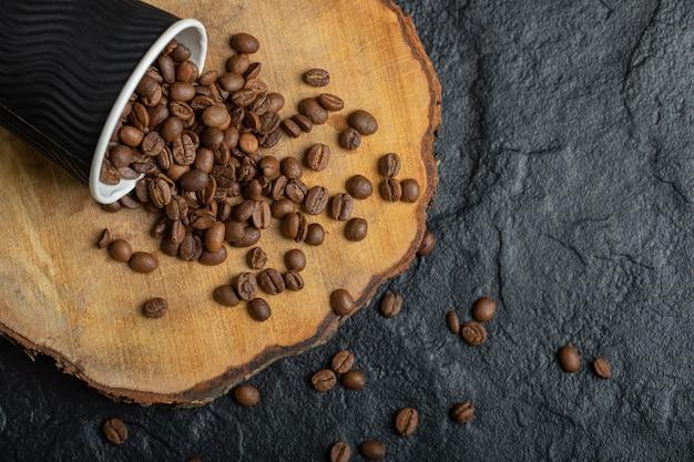 Eine schwarze tasse voller kaffeebohnen auf holzbrett.