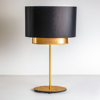 Eine schwarzgoldlampe der vorderansicht, die auf dem weißen hintergrund exquisit dekoriert wurde