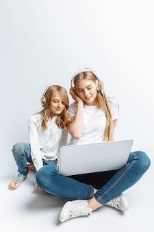 Eine schwester oder eine junge mutter mit ihrer tochter, die einen film auf meinem laptop sieht, lustig, lachend