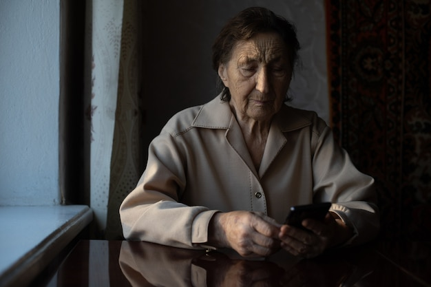 Eine sehr alte ältere kaukasische großmutter mit tiefen falten sitzt zu hause und benutzt ihr smartphone auf der frontkamera des ausgestreckten arms für einen videoanruf.