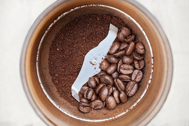 Eine seite der elektrischen kaffeemühle aus metall mit ganzen kaffeekörnern, eine andere mit gemahlenem