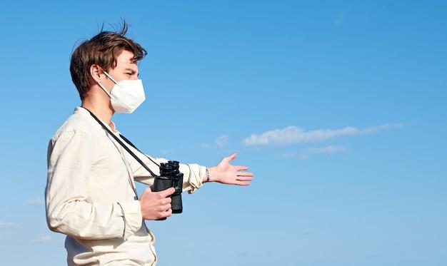 Eine seitenansicht eines attraktiven jungen mannes aus spanien mit einem fernglas, das eine maske trägt, die verwirrt in die ferne starrt