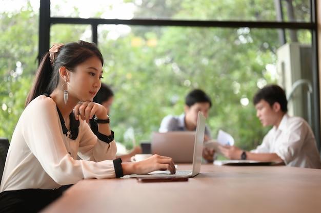 Eine sekretärin benutzt einen computer-laptop, während sie im besprechungsraum sitzt.