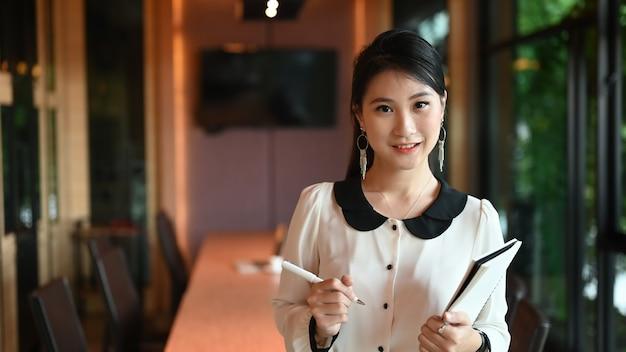 Eine sekretärin steht, während sie papierkram und stift in den händen über einem besprechungsraum hält