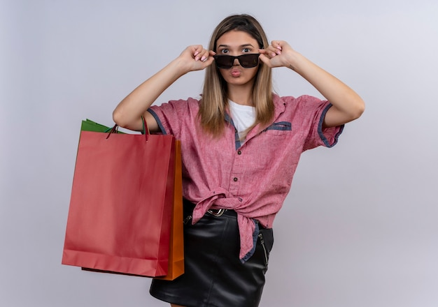 Eine selbstbewusste junge frau, die rotes hemd trägt, das einkaufstaschen hält, während durch sonnenbrille auf einer weißen wand schaut