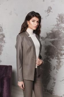 Eine selbstbewusste junge frau mit langen, schönen haaren in einem modischen grauen anzug-business-modekonzept