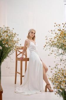 Eine sexy blonde frau in einem schönen weißen kleid steht zu hause zwischen sträußen wilder blumen