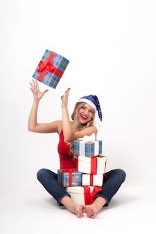 Eine sexy blondine mit den großen brüsten, die unter weihnachtsgeschenken sitzen