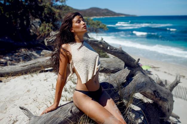 Eine sexy brünette frau mit langen haaren, die am strand aufwirft und auf stamm des alten baumes, korsika-insel, frankreich sitzt.