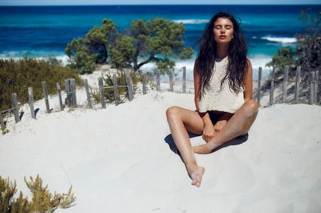 Eine sexy brünette frau mit langen haaren, die mit geschlossenen augen auf dem heißen sand am strand sitzt, hat entspannungszeit auf korsika, meereswellen und weißem strandhintergrund. horizontale ansicht.