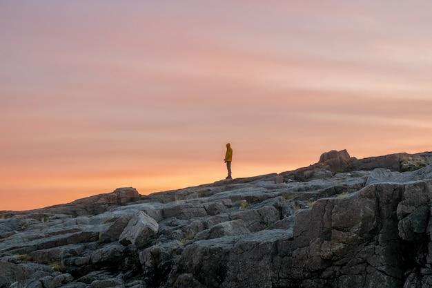 Eine silhouette, eine figur auf einer steilen klippe gegen den dunklen sonnenuntergangshimmel.