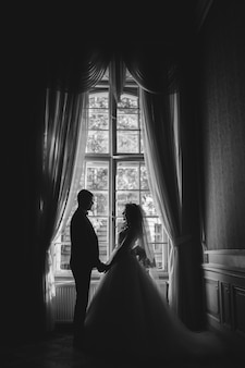 Eine silhouette einer braut und bräutigam bleiben vor einem schmalen wind