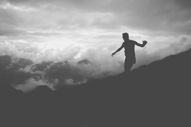 Eine silhouette eines athleten, der die hänge eines berges hinunterläuft