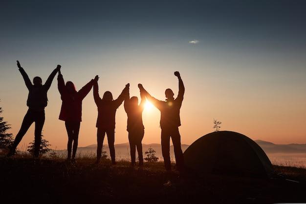 Eine silhouette von gruppenleuten hat spaß auf der spitze des berges in der nähe des zeltes während des sonnenuntergangs.