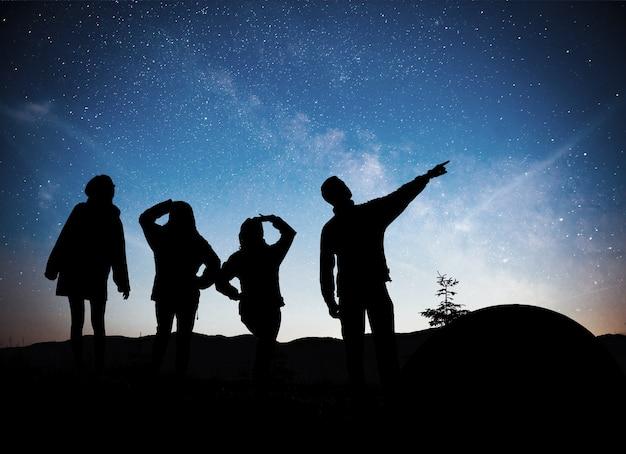 Eine silhouette von gruppenleuten hat spaß auf der spitze des berges nahe dem zelt während des hintergrunds der milchstraßengalaxie auf einem hellen sternhimmelton.