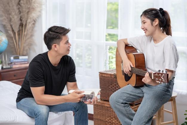 Eine sitzende frau spielt gitarre und ein mann hält ein buch und singt.