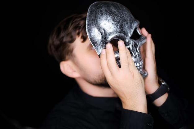 Eine skelettmaske, die ein mann auf sein gesicht setzen möchte