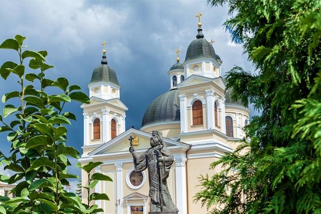 Eine skulptur eines heiligen in der nähe einer orthodoxen steinkirche auf dem hintergrund eines gewitterhimmels.