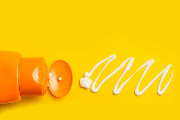 Eine sonnencremeflasche auf gelbem grund mit einem zug