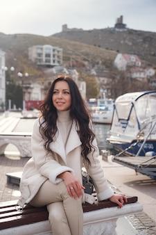 Eine sorglose kaukasische frau in beige kleidung, die den blick auf das meer an einem warmen, windigen tag genießt