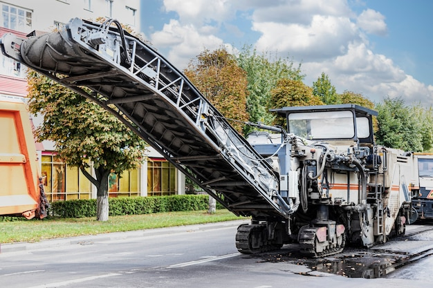 Eine spezielle maschine schneidet den asphalt. der techniker entfernt den alten asphalt und verlädt ihn auf einen muldenkipper. straßenreparatur, asphaltaustausch, bauarbeiten.