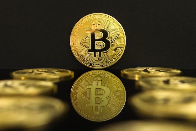 Eine spiegelreflexion von goldenen btc-münzen. die münze von bitcoin befindet sich auf einem schwarzen tisch und einem schwarzen hintergrund.