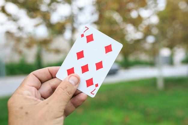 Eine spielkarte in der hand zeigen