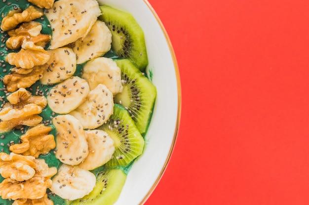 Eine spirulina-smoothie-schüssel mit bananen-, walnuss-, kiwi- und chiasamen auf rotem hintergrund