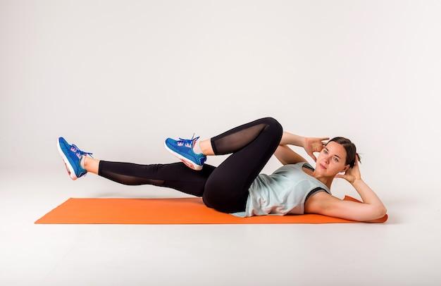 Eine sportlerin auf einer orangefarbenen matte führt übungen für schräge muskeln der presse auf einem weiß aus, das mit platz für text isoliert ist