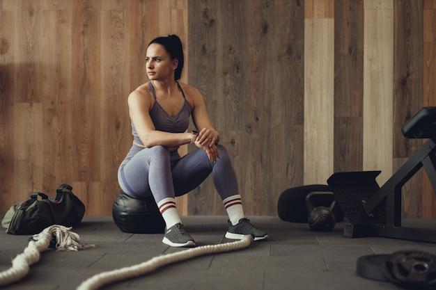 Eine sportlerin mit einer aufgepumpten beute hockt mit einem phyto-ball in der nähe der wand