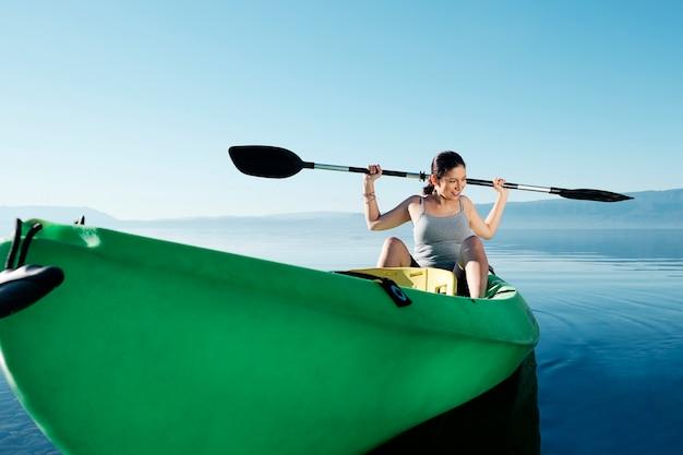 Eine sportlerin sitzt in einem kajak mit ihren paddeln auf den schultern im meer gegen den blauen himmel.