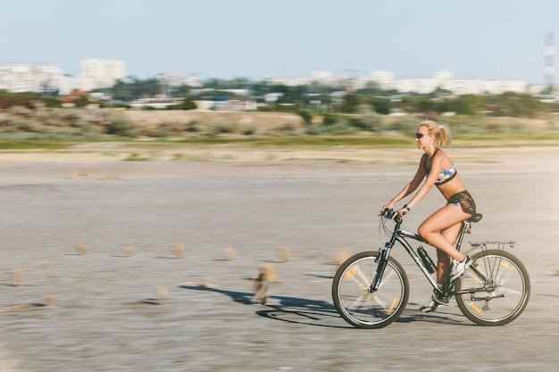 Eine sportliche blonde frau in einem bunten anzug fährt an einem sonnigen sommertag mit hoher geschwindigkeit in einer wüstengegend fahrrad. fitness-konzept.