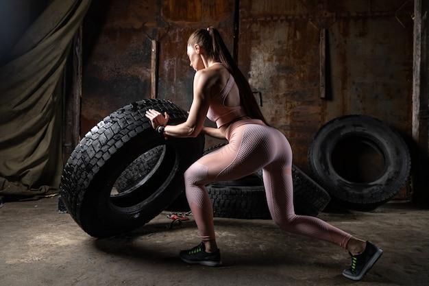 Eine sportliche frau in einem rosa oberteil und leggings, die sit-ups machen