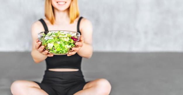 Eine sportliche frau in sportkleidung sitzt mit gesundem essen auf dem boden.