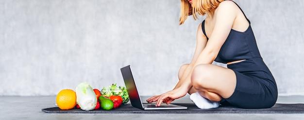 Eine sportliche frau in sportkleidung sitzt mit gesundem essen und ihrem laptop auf dem boden