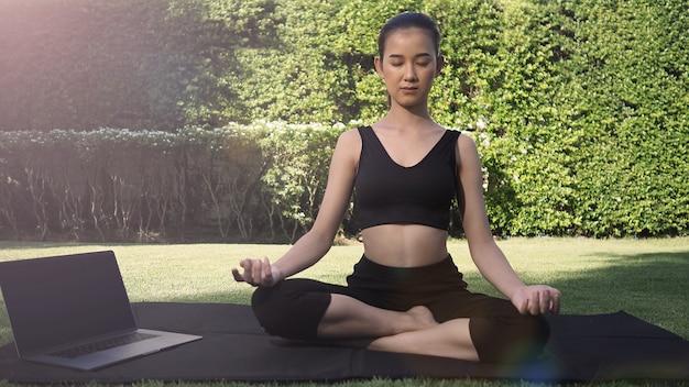 Eine sportliche frau oder ein online-trainer in sportbekleidung sitzt und praktiziert yoga auf der matte