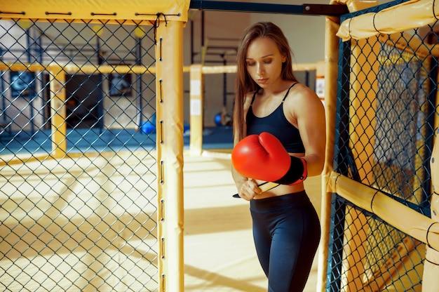 Eine sportliche weibliche mma-kämpferin in boxhandschuhen posiert in einem käfig im fitnessstudio